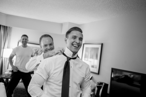 Groomsmen doing up their ties before the wedding