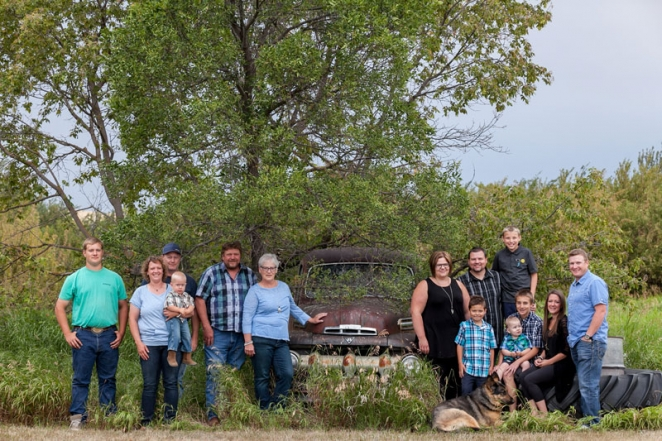 Family photograph on the farm with old rusty truck and tree by Collin Stumpf Photography