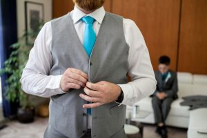 Groom doing up buttons