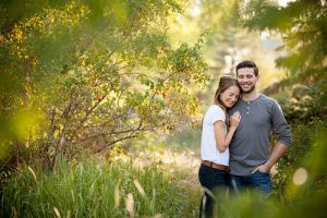 couple cuddled together in trees and golden evening light
